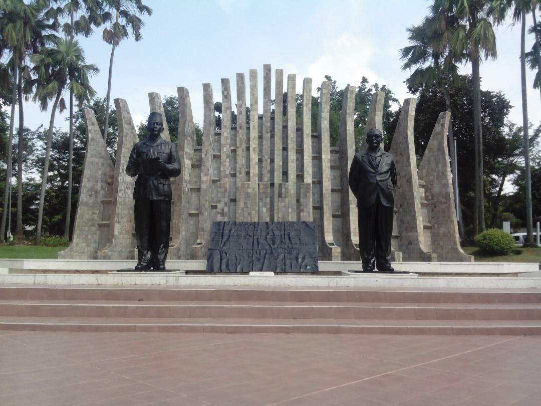 monumen dua patung Soekarno-Hatta berukuran besar yang berdiri berdampingan, mirip dengan dokumentasi foto ketika naskah proklamasi pertama kali dibacakan